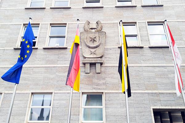 Ausschnitt der Fassade des Rathauses in Halle (Saale) mit dem Stadtwappen, davor stehen 4 Flaggen, die europäische, die deutsche, die des Landes Sachsen-Anhalt sowie die hallesche Flagge.