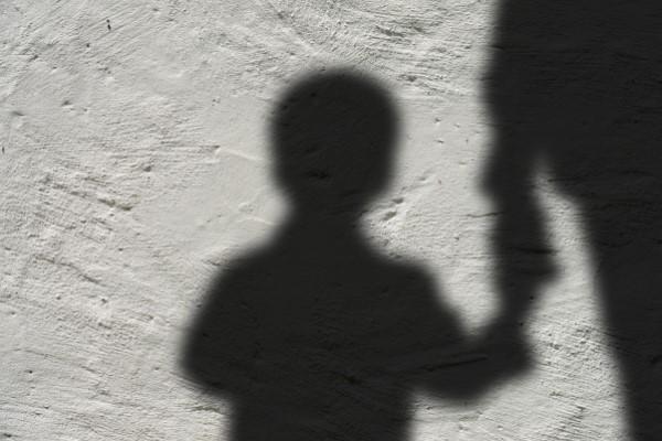 Schatten eines Kindes, welches an die Hand genommen wird von einer größeren Person