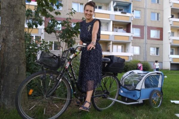 Stadträtin Dörte Jacobi auf ihrem Fahrrad vor einem Wohnhaus in Heide-Nord